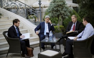 U.S. Secretary of State John Kerry (C) and State Department Chief of Staff Jon Finer (L) meet with members of the U.S. delegation at the garden of the Palais Coburg hotel where the Iran nuclear talks meetings are being held in Vienna, Austria July 10, 2015. Iran and major powers gave themselves until Monday to reach a nuclear agreement, their third extension in two weeks, as Tehran accused the West of throwing up new stumbling blocks to a deal. REUTERS/Carlos Barria  - RTX1JX4V