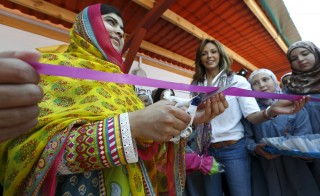 "Nobel Peace Prize laureate Malala Yousafzai (L) cuts a ribbon near Noura Jumblatt (R), founder of the NGO Kayany Foundation, at a school for Syrian refugee girls, built by the foundation, in Lebanon's Bekaa Valley July 12, 2015. Yousafzai celebrated her 18th birthday in Lebanon on Sunday by opening the school and called on world leaders to invest in ""books not bullets."" The Malala Fund, a non-profit organisation that supports local education projects, paid for the school. Photo by Jamal Saidi/Reuters"