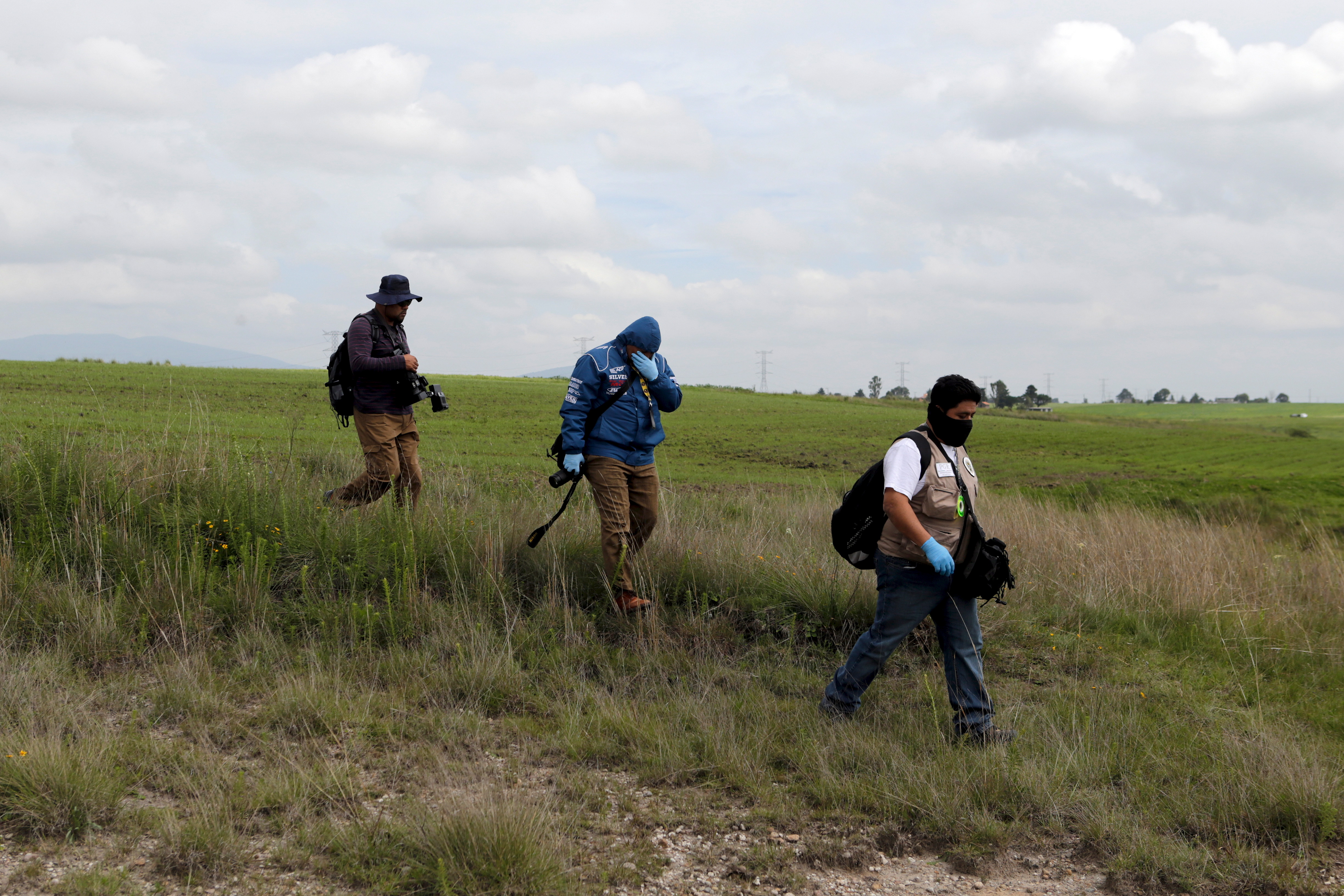 "Forensic technicians from Mexico's Attorney General office walk toward a construction where a tunnel, connecting with the Altiplano Federal Penitentiary and used by drug lord Joaquin 'El Chapo' Guzman to escape, was located in Almoloya de Juarez, on the outskirts of Mexico City, July 12, 2015. National Security Commissioner Monte Alejandro Rubido said 18 officials from the penitentiary had been taken in for interrogation at the unit of the Attorney General's office specializing in organized crime. Mexico's most notorious drug lord Joaquin ""El Chapo"" Guzman escaped from high security prison in a tunnel built under his cell, the government said, his second jailbreak in 15 years and a major embarrassment for President Enrique Pena Nieto.  REUTERS/Tomas Bravo  - RTX1K3N5"