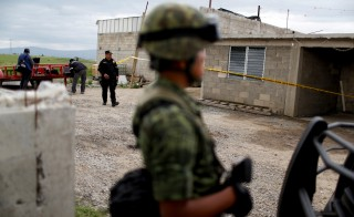 "A soldier and policemen keep watch outside a warehouse where a tunnel, connected to the Altiplano Federal Penitentiary and used by drug lord Joaquin 'El Chapo' Guzman to escape, was located in Almoloya de Juarez, on the outskirts of Mexico City, July 12, 2015.Mexico's most notorious drug lord, Joaquin ""El Chapo"" Guzman, broke out of a high security prison on Saturday night for the second time, escaping in a tunnel built right under his cell, and heaping embarrassment on President Enrique Pena Nieto. The kingpin snuck out of the prison through a subterranean tunnel more than 1.5 km (1 mile) long that ended in a building site in the local town, National Security Commissioner Monte Alejandro Rubido told a news conference on Sunday. REUTERS/Tomas Bravo - RTX1K4AJ"