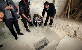 "Mexico's Attorney General Arely Gomez Gonzalez, second from right, looks into the entrance of a tunnel connected to the Altiplano Federal Penitentiary and used by drug lord Joaquin ""El Chapo"" Guzman to escape, in Almoloya de Juarez, on the outskirts of Mexico City, July 12, 2015. Photo by Mexican Attorney General's Office/Handout via Reuters"