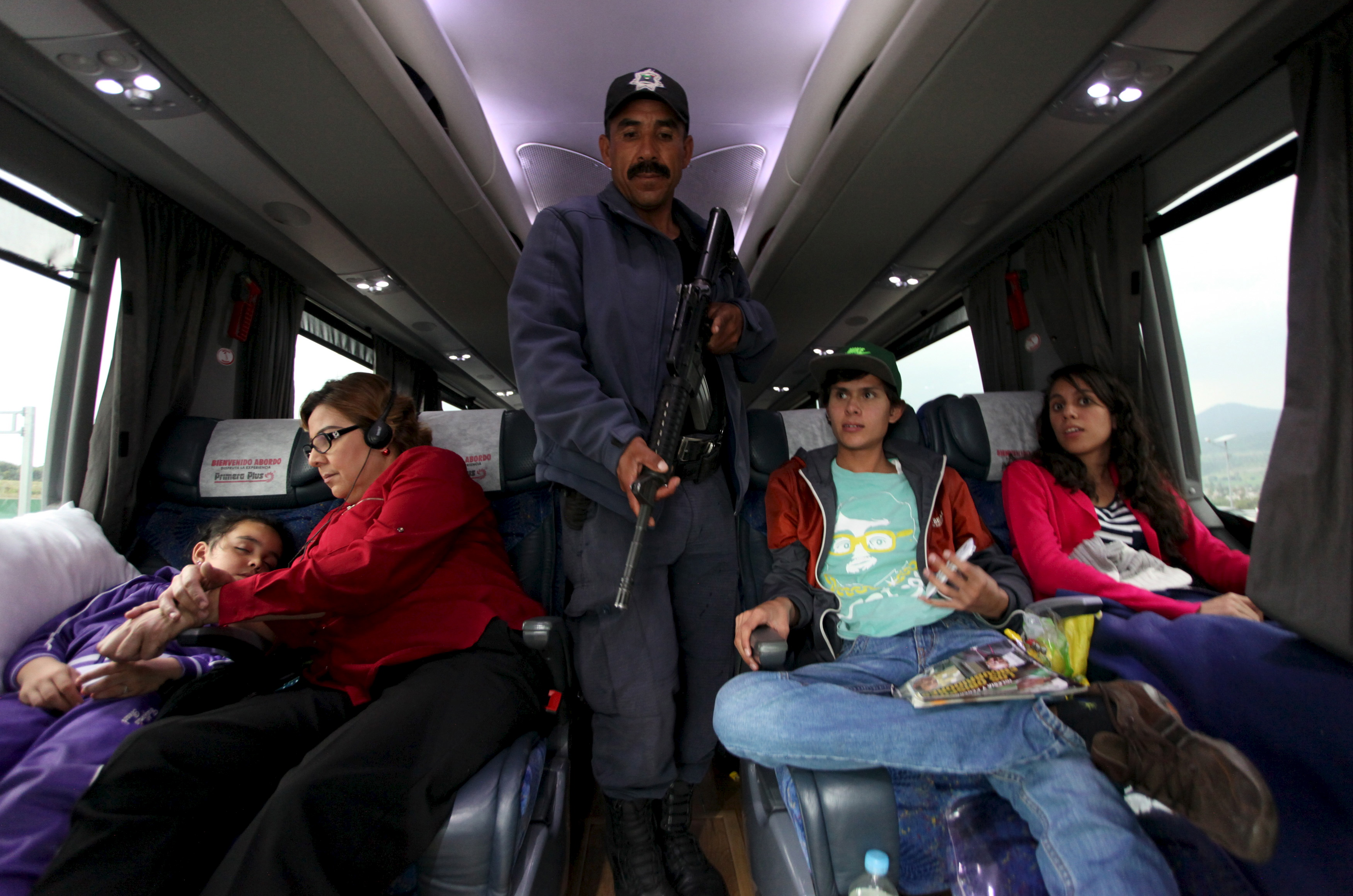 "A police officer inspects a passenger bus at a checkpoint on an highway in Contepec, in Michoacan state, July 12, 2015. Mexico's most notorious drug lord, Joaquin ""El Chapo"" Guzman, broke out of a high-security prison July 11 for the second time, escaping in a tunnel built right under his cell, and heaping embarrassment on President Enrique Pena Nieto. Photo by Alan Ortega/Reuters"