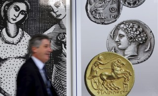 A man walks past pictures of ancient coins in central Athens, Greece, July 13, 2015.  Euro zone leaders agreed on a roadmap to a possible third bailout for near-bankrupt Greece on Monday, but Athens must enact key reforms this week before they will start talks on a financial rescue to keep it in the European currency area. REUTERS/Jean-Paul Pelissier  - RTX1K69J