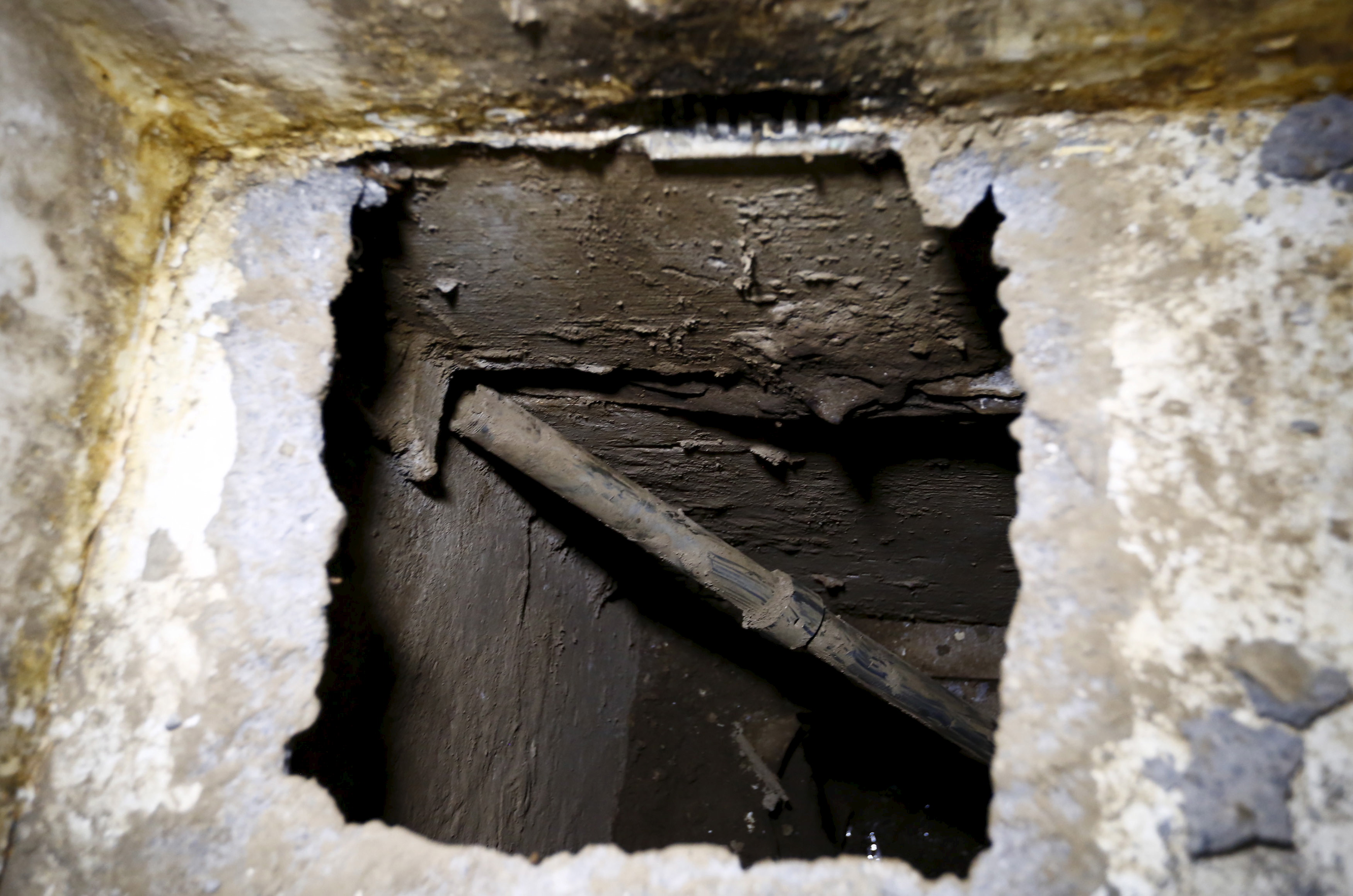 "A view of the opening of a tunnel, which is connected to a warehouse, inside drug lord Joaquin ""El Chapo"" Guzman's cell in the Altiplano Federal Penitentiary, where he escaped from, in Almoloya de Juarez, on the outskirts of Mexico City, July 15, 2015. U.S. law enforcement officials met with agents of the Mexican attorney general's office this week to share information related to the escape from prison of Guzman and coordinate efforts to apprehend him, a Mexican government official said on Wednesday. REUTERS/Edgard Garrido - RTX1KGFS"