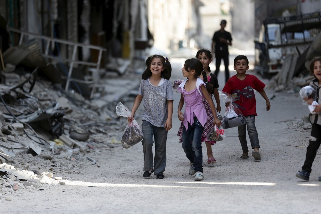 Children carry bags of new clothes days before Eid al-Fitr in Jobar, a suburb of Damascus, Syria on July 15, 2015. Photo by Bassam Khabieh/Reuters