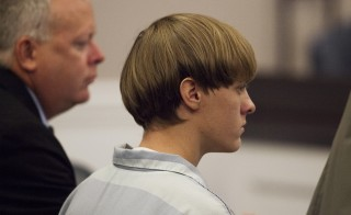 Dylann Roof, charged with murdering nine worshippers at a historic black church in Charleston last month, listens to the proceedings with assistant defense attorney William Maguire during a hearing at the Judicial Center in Charleston