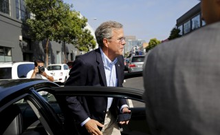 Republican presidential candidate Jeb Bush exits an Uber vehicle as he arrives at Thumbtack, a consumer service connecting experienced professionals in San Francisco, California, July 16, 2015. Companies that are a part of the sharing economy, like Uber, are presenting a policy challenge for Democrats. Photo by Robert Galbraith/Reuters