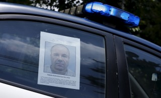 "A police vehicle is seen a poster with a photo of drug lord Joaquin ""El Chapo"" Guzman offering a reward of 60 million Mexican pesos for information along a street in Mexico City on July 16, 2015. Photo by Henry Romero/Reuters"