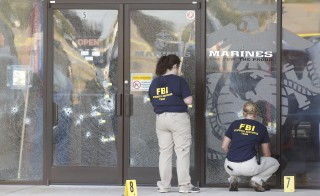 FBI agents work the scene at the Armed Forces Career Center in Chattanooga, Tennessee July 16, 2015. Four Marines were killed on Thursday by a gunman who opened fire at two military offices in Chattanooga, Tennessee, before being fatally shot in an attack officials called a brazen, brutal act of domestic terrorism. REUTERS/Tami Chappell  - RTX1KM12