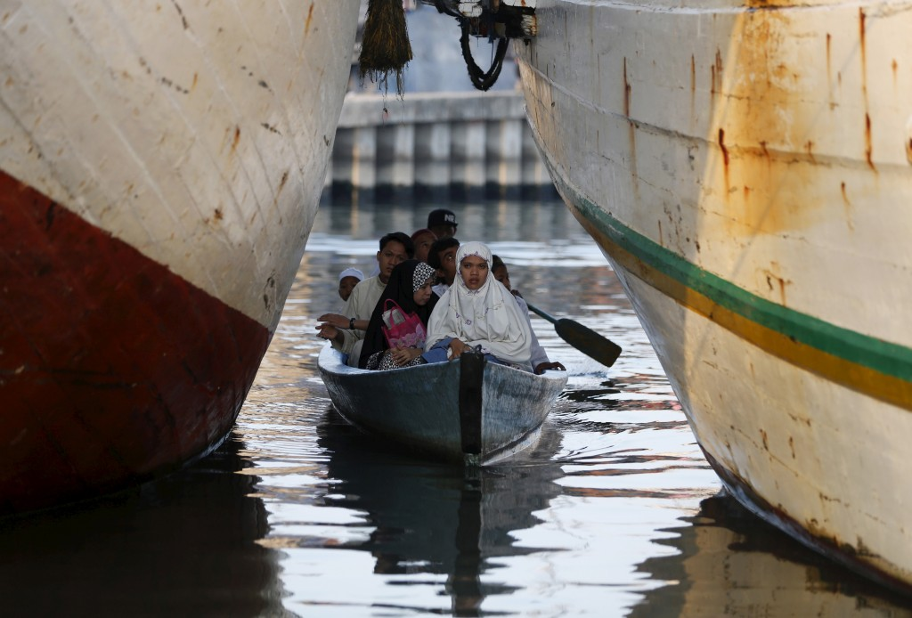 Muslims from a nearby neighborhood arrive by boat to attend Eid al-Fitr prayers at Sunda Kelapa port in Jakarta, Indonesia on July 17, 2015. Indonesia, which has the world's largest Muslim population, celebrates Eid al-Fitr with mass prayers and family visits to mark the end of the holy fasting month of Ramadan.  Photo by Darren Whiteside/Reuters