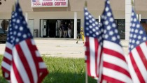 American flags line a memorial as FBI agents continue their investigation at the Armed Forces Career Center in Chattanooga, Tennessee July 17, 2015. Four U.S. Marines were killed on Thursday by a suspected gunman the FBI has confirmed as Mohammod Youssuf Abdulazeez, who opened fire at two military offices in Chattanooga before being fatally shot by police.   REUTERS/Tami Chappell - RTX1KQYT