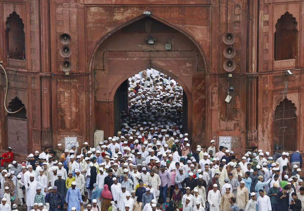 Muslims leave through a gate of the Jama Masjid (Grand Mosque) after offering prayers on the occasion of Eid al-Fitr in the old quarters of Delhi, India on July 18, 2015. Eid al-Fitr begins with morning prayers in large, open, community areas. Photo by Anindito Mukherjee/Reuters