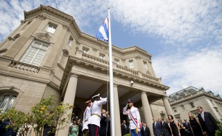 Cuban Foreign Minister Bruno Rodriguez, center, raises the Cuban national flag over their embassy in Washington Monday. The flag was raised over Havana's embassy in Washington for the first time in 54 years as the United States and Cuba formally restore relations. Photo by Andrew Harnik/Pool/via Reuters