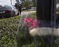 A police officer stands at the entrance to a movie theatre, near flowers left for victims of a Thursday night shooting, in the theatre in Lafayette, Louisiana July 24, 2015. John Russell Houser, an Alabama drifter, opened fire inside the crowded movie theater, killing two women, police said, in the latest act of random gun violence to shock the United States. REUTERS/Lee Celano - RTX1LOGL