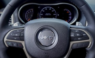 The Jeep logo is seen on the steering wheel of a 2015 Jeep Grand Cherokee at a car dealership in New Jersey, July 24, 2015. Fiat Chrysler will recall 1.4 million vehicles in the United States to install software to prevent hackers from gaining remote control of the engine, steering and other systems. Photo by Eduardo Munoz/Reuters