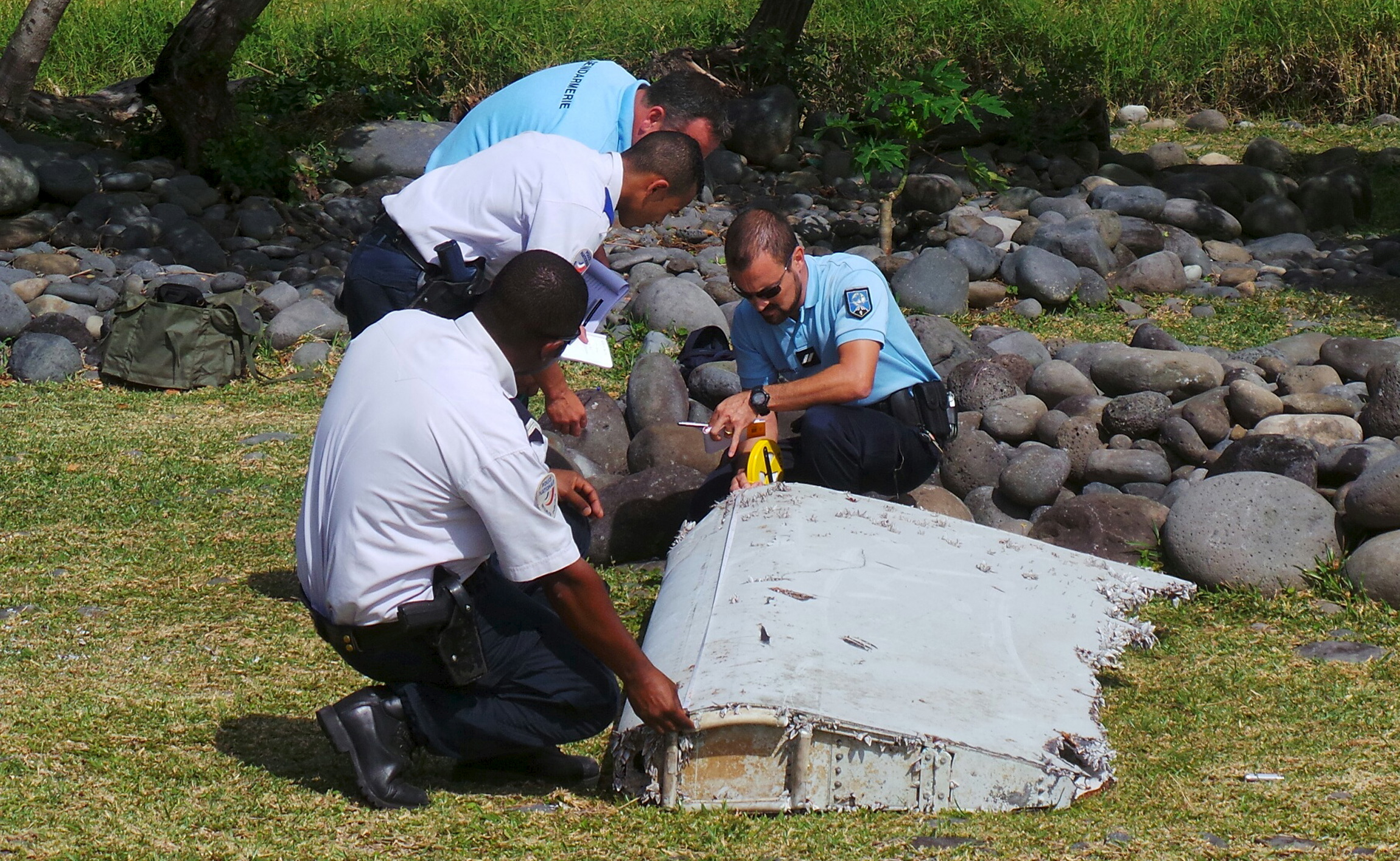 French gendarmes and police inspect a large piece of plane debris which was found on the beach in Saint-Andre, on the French Indian Ocean island of La Reunion, July 29, 2015. France's BEA air crash investigation agency said it was determining whether it came from Malaysia Airlines Flight MH370, which vanished last year. Picture taken July 29, 2015. Photo by Prisca Bigot/Reuters