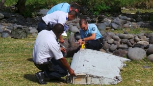French gendarmes and police inspect a large piece of plane debris which was found on the beach in Saint-Andre, on the French Indian Ocean island of La Reunion, July 29, 2015. France's BEA air crash investigation agency said it was examining the debris,  in coordination with Malaysian and Australian authorities, to determine whether it came from Malaysia Airlines Flight MH370, which vanished last year in one of the biggest mysteries in aviation history. Picture taken July 29, 2015.     REUTERS/Zinfos974/Prisca Bigot      TPX IMAGES OF THE DAY      - RTX1MCP2