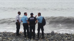 French gendarmes and police stand on the beach where a large piece of plane debris was found in Saint-Andre, on the French Indian Ocean island of La Reunion, July 29, 2015. France's BEA air crash investigation agency said it was examining the debris,  in coordination with Malaysian and Australian authorities, to determine whether it came from Malaysia Airlines Flight MH370, which vanished last year in one of the biggest mysteries in aviation history. Picture taken July 29, 2015.     REUTERS/Zinfos974/Prisca Bigot  - RTX1ME0M