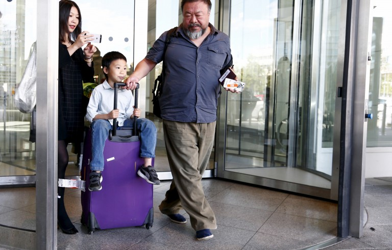 Dissident Chinese artist Ai Weiwei, right, with his son Ai Lao leave the airport in Munich, Germany on July 30, 2015. Photo by Michaela Rehle/Reuters