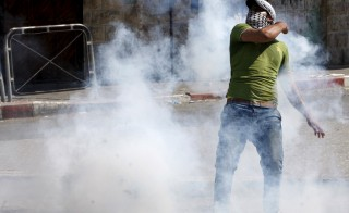 A Palestinian protester throws a tear gas canister, initially fired by Israeli troops, during clashes in the West Bank city of Hebron July 31, 2015. Suspected Jewish attackers torched a Palestinian home in the occupied West Bank on Friday, killing an 18-month-old toddler and seriously injuring three other family members, an act that Israel's prime minister described as terrorism. Photo by Mussa Qawasma/Reuters