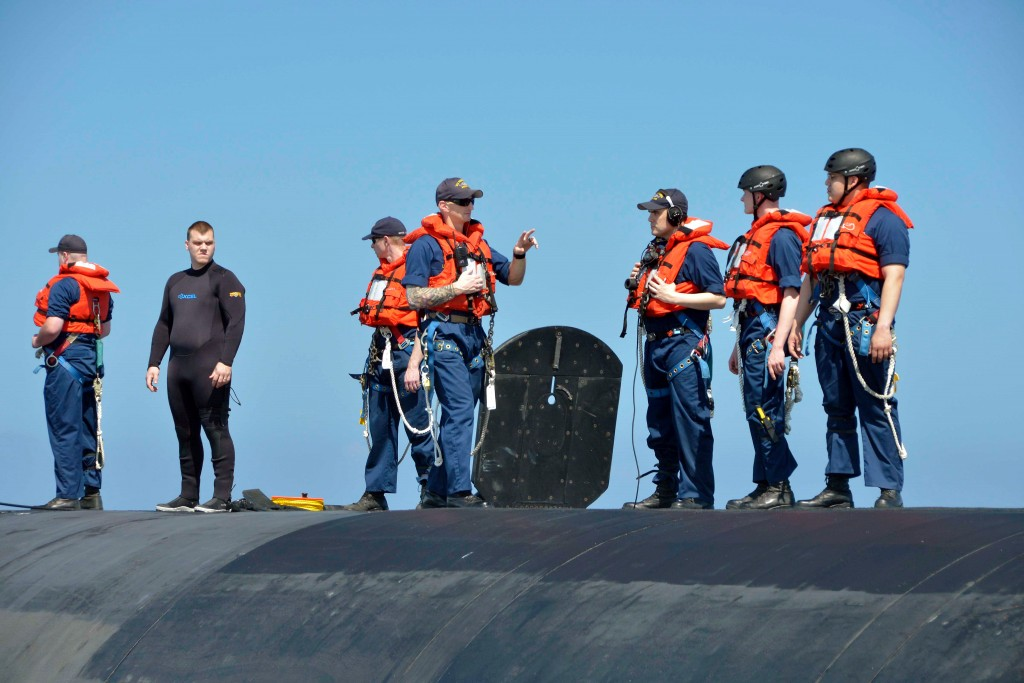 A diver stands ready to jump into the ocean if anyone accidentally falls off the submarine. Photo by Dan Sagalyn