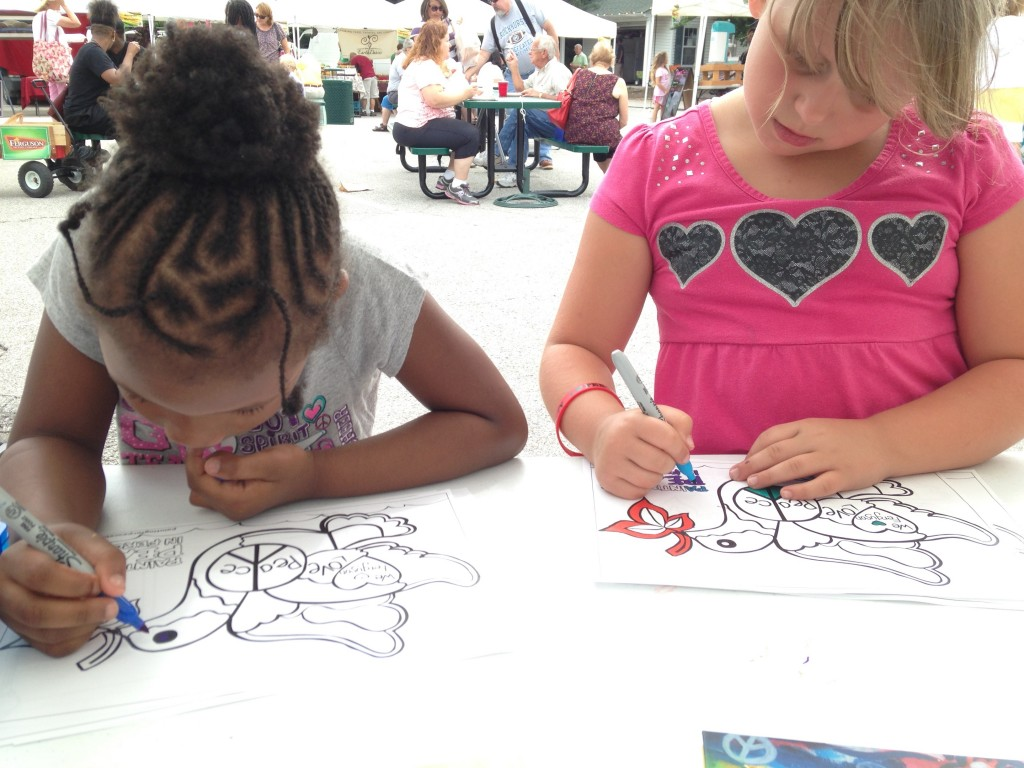 """Two kids color at the Ferguson farmers' market during a book signing for """"Painting in Peace in Ferguson"""" July 25, 2015. Photo by Carol Klein"""