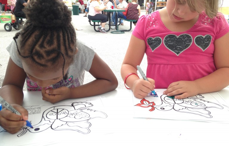 "Two kids color at the Ferguson farmers' market during a book signing for ""Painting in Peace in Ferguson"" July 25, 2015. Photo by Carol Klein"