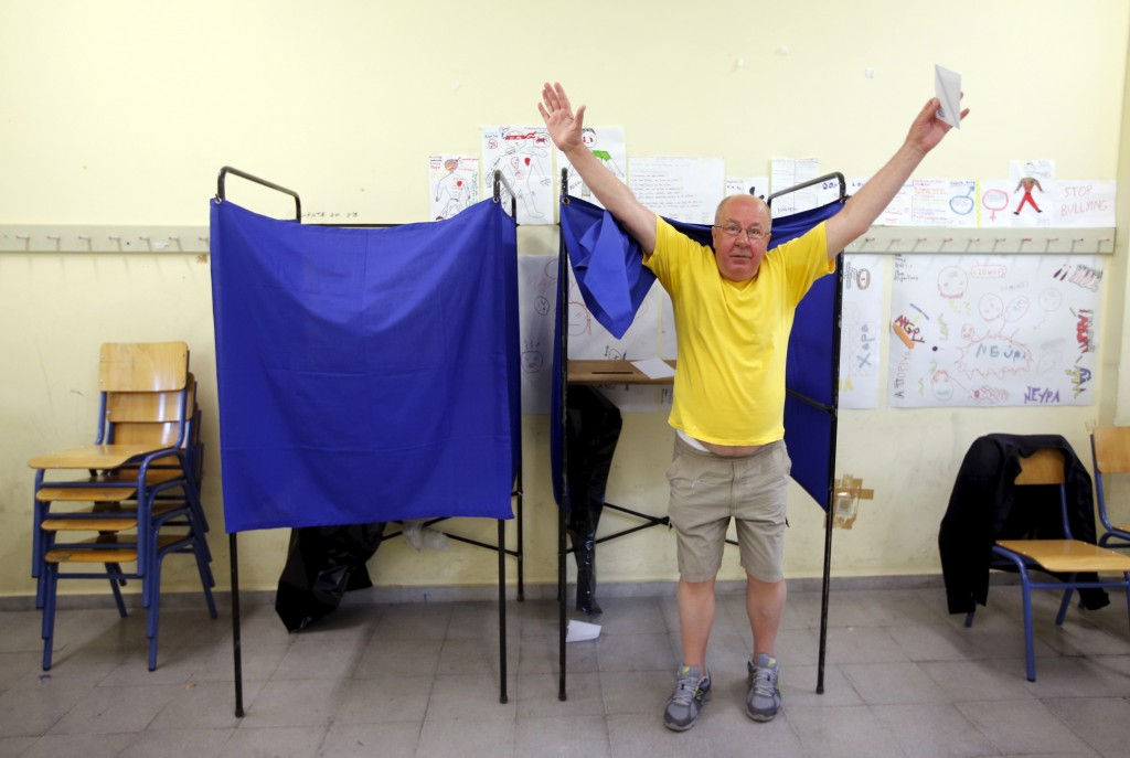 A man raises his arms as he leaves a polling booth during a referendum vote in Athens, Greece, on July 5, 2015. Greece voted Sunday on whether to accept more austerity in exchange for international aid, in a high-stakes referendum likely to determine whether it leaves the eurozone after seven years of economic pain.    Photo by Jean-Paul Pelissier/Reuters