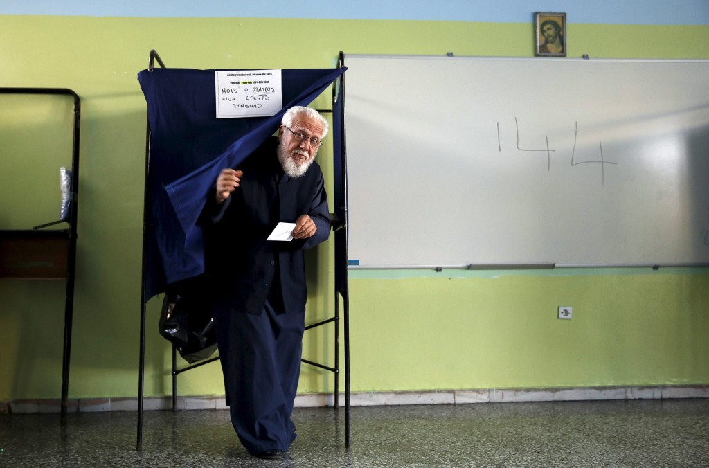 A Greek Orthodox priest exits a voting booth holding a ballot at a polling station in Athens, Greece, on July 5, 2015. Greece voted on Sunday on whether to accept more austerity in exchange for international aid, in a high-stakes referendum likely to determine whether it leaves the eurozone after seven years of economic pain. Photo by Yannis Behrakis/Reuters