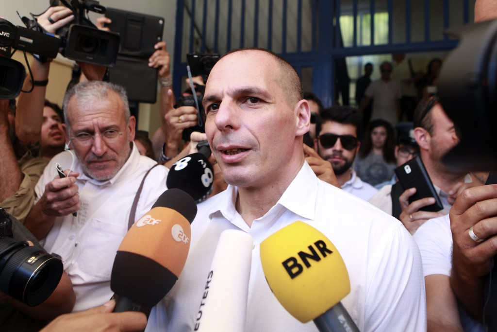 Greek Finance Minister Yanis Varoufakis is surrounded by media as he leaves a polling station during a referendum in Athens, Greece, on July 5, 2015. Greece voted Sunday on whether to accept more austerity in exchange for international aid, in a high-stakes referendum likely to determine whether it leaves the eurozone after seven years of economic pain.   Photo by Dimitris Michalakis/Reuters