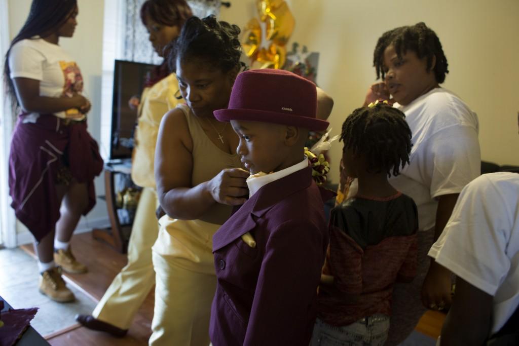 Young boy gets dressed for Original Big Nine Social Aid