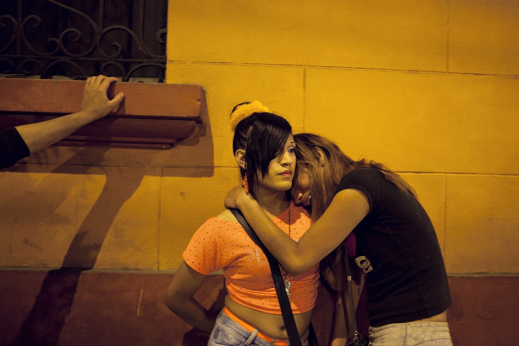 """Jordy, left, gives her friend a shoulder to cry on after she found out that her boyfriend was cheating on her with another transwoman. According to anthropologist Ximena Salazar the structures and traditions of gender are very rigid in Peruvian society, thus making it very easy for society to discriminate those who do not fulfill traditional roles. """"The family is the first big social space where the female trans is going to have a fight.Ó Because of this constant fight, many leave home and move to Lima where they know there is a network already waiting. [Sex work] is a social world complete with friends and enemies. Their real family rejects them, so their chosen family is also there, said Salazar."""