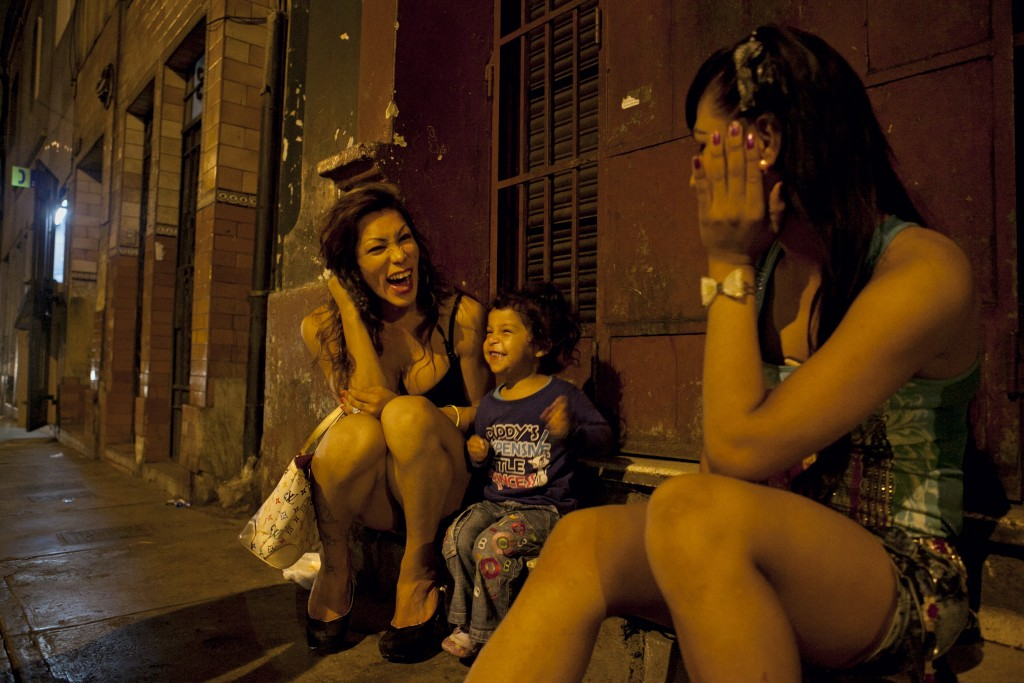 Danuska, left, and Oriana, right, talk with a young girl and her mother, not pictured, on the street while experiencing down time during work.