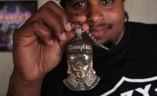 "Eric Wright Jr., the son of N.W.A.'s Eazy-E, wears a bejeweled necklace of his father, complete with the rapper's trademark Locs sunglasses and black ""Compton"" hat, all part of the uniform that solidified West Coast bad boy style. Photo by Joshua Barajas/PBS NewsHour"