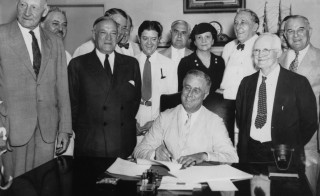 President Franklin D. Roosevelt signs the Social Security Act on Aug. 14, 1935. From left to right, Robert Lee Doughton, chairman of the House Ways and Means Committee, Edwin E. Witte, Director of the President's Social Security Committee, with Senator Robert F. Wagner, co-author of the bill behind him, Senator Robert La Follette, Senator Augustine Lonergan, Labor Secretary Frances Perkins, Senator William H. King, Rep. David John Lewis, co-author of the bill and Senator Joseph F. Guffey. Photo by FPG/Archive Photos/Getty Images
