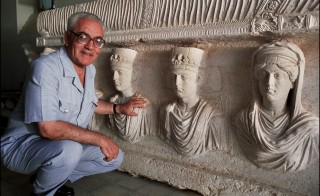 Archaeologist Khaled al-Asaad is pictured here in September 2002 in front of a sarcophagus in Palmyra, Syria. Photo by Marc Deville/Gamma-Rapho via Getty Images
