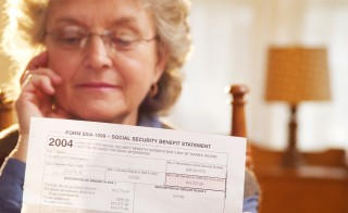 Mature adult looking at Social Security documents. Photo by Jim McGuire/Getty Images