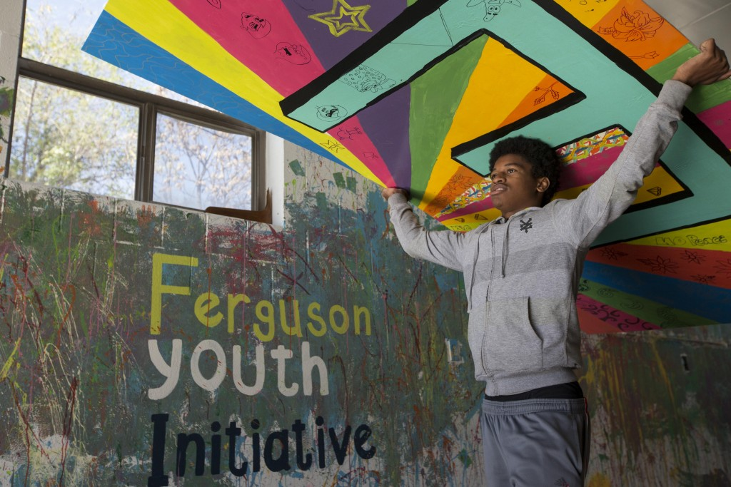 FERGUSON, MO - OCTOBER 31:  George Taylor, 17, moves sections of a mural outside to be polyurethaned on Saturday, Nov. 1, 2014 in Ferguson, Missouri. The community art project was organized by Ferguson Youth Initiative, a nonprofit organization developing programs for young people in the St. Louis suburb. (Photo by Whitney Curtis for The Washington Post via Getty Images)
