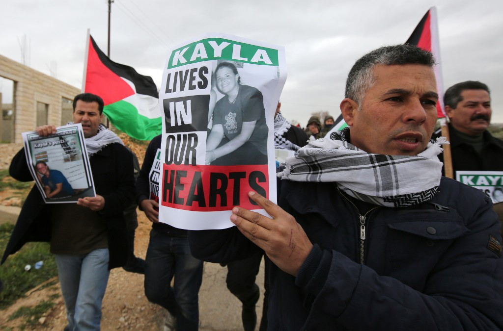 "Palestinian protesters hold placard to protest against ""terrorism"" on February 13, 2015 before a demonstration against Jewish settlements in the West Bank village of Bilin, west of Ramallah. The poster shows a picture of US aid worker Kayla Mueller, who died as a hostage of Islamic State (IS) group jihadists. AFP PHOTO/ABBAS MOMANI        (Photo credit should read ABBAS MOMANI/AFP/Getty Images)"