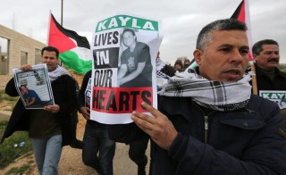 """Palestinian protesters hold placard to protest against """"terrorism"""" on February 13, 2015 before a demonstration against Jewish settlements in the West Bank village of Bilin, west of Ramallah. The poster shows a picture of US aid worker Kayla Mueller, who died as a hostage of Islamic State (IS) group jihadists. AFP PHOTO/ABBAS MOMANI        (Photo credit should read ABBAS MOMANI/AFP/Getty Images)"""