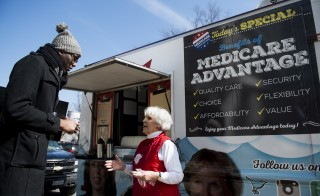 UNITED STATES - MARCH 9: Carol Berman, of West Palm Beach, Fla., speaks with pedestrians about the need for policymakers to protect Medicare Advantage benefits during the Coalition for Medicare Choices' Medicare Advantage Food Truck stop on North Capitol Street in Washington on Monday, March 9, 2015. Seniors shared cookies, coffee and personal stories about  Medicare Advantage while standing outside of the food truck. (Photo By Bill Clark/CQ Roll Call)