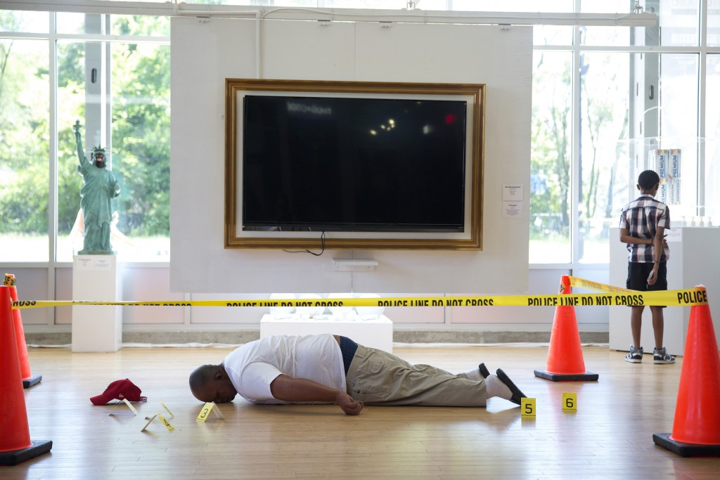 "A visitor stands near the ""Angelitos Negros"" art installation depicting a life-size replica of the body of Michael Brown and the crime scene where he was shot by police officer Darren Wilson in Ferguson, Mo. last year, at the ""Confronting Truths: Wake Up!"" exhibition featuring works by New Orleans artist Ti-Rock Moore at Gallery Guichard Fine Art Gallery on July 12, 2015 in Chicago. Moore's artist statement about this piece reads: ""Angelitos Negros is a reflection on Michael Brown's brutal murder by the Ferguson, Missouri police last year. The installation introduces a silicone replica of Brown's dead body with Eartha Kitt's controversial 1950s song 'Angelitos Negros' or 'Little Black Angels' playing in the backdrop, calling attention to the racial injustices that existed then and remain devastatingly relevant today."" (Erin Hooley/Chicago Tribune/TNS via Getty Images)"