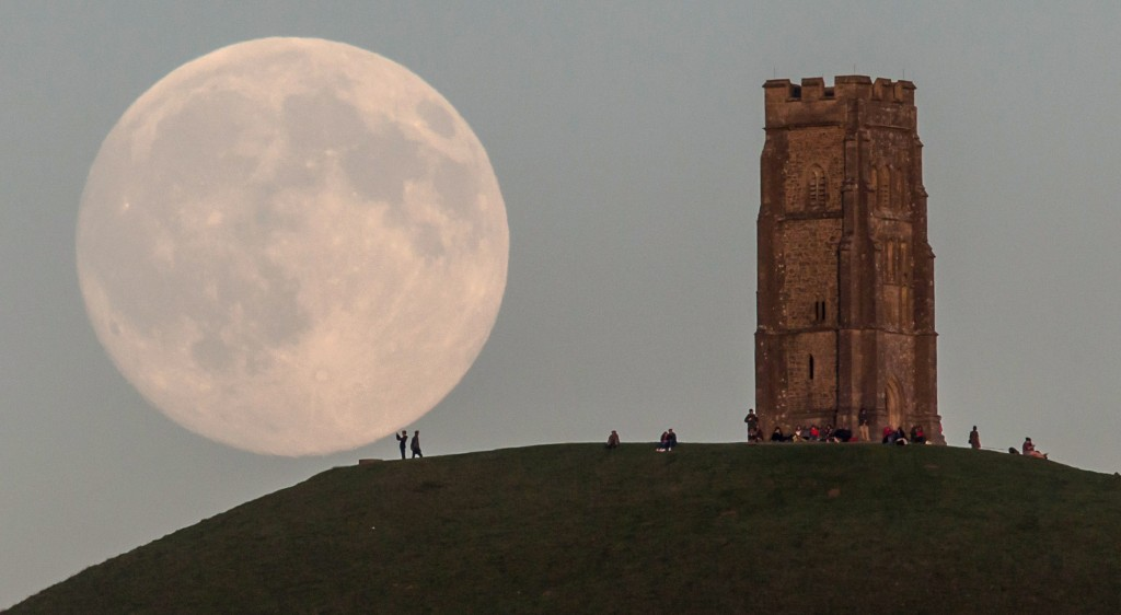 The blue moon rises over people gathered on Glastonbury Tor in Somerset, England. Photo by Matt Cardy/Getty Images.