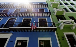 A Puerto Rico flag hangs from a building in Old San Juan, Puerto Rico, on Friday, August 14, 2015. Photographer: Derick E. Hingle/Bloomberg