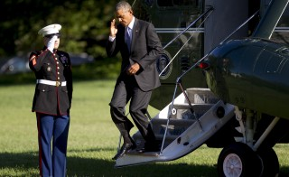President Barack Obama salutes while exiting Marine One after landing on the South Lawn of the White House in Washington, D.C., on Aug. 25. Photo by Andrew Harrer/Bloomberg via Getty Images