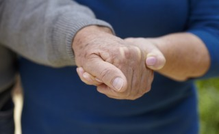 Woman holding older man's hand to assist with walking