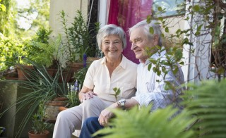 Senior couple sitting on back door steps. Photo by Cultura/Attia-Fotografie/Getty Images