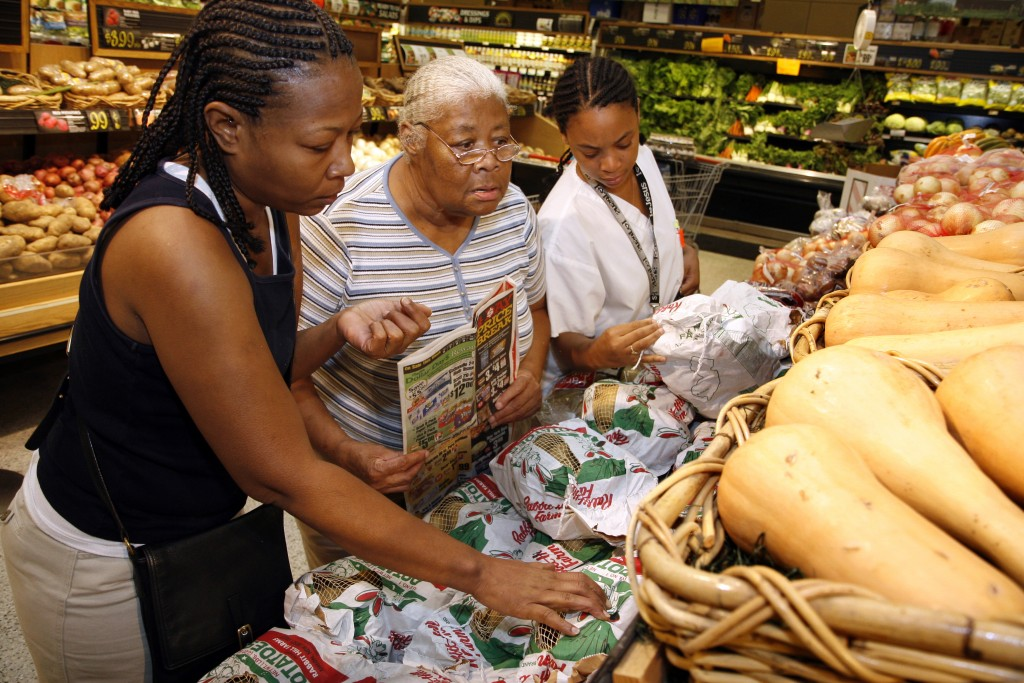 NEGATIVE# josephm 182848--SLUG-NA/GROCERY--DATE-08/08/06-- ShopRite Grocery store, 296 Island Avenue, Phildelphia, PA.--PHOTOGRAPHER-MARVIN JOSEPH/TWP--CAPTION-Efforts by community activists bring more grocery stores to poor neighborhoods. PICTURED, from left to right, Sharita Henderson, Geraldine Henderson, and Shantay Henderson search for the potatoes that are on sale at ShopRite.  (Photo by Marvin Joseph/The Washington Post/Getty Images)
