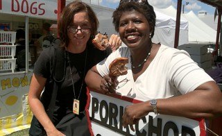 Gwen and NewsHour producer Mary Jo Brooks try pork chop on a stick at the 2011 Iowa State Fair. Photo by PBS NewsHour