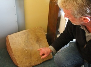 Archaeologist Nick Card shows off a Neolithic carved stone slab unearthed from one of the 20 structures at the Ness of Brodgar, in Orkney, Scotland.  Photo by Lorna Baldwin.